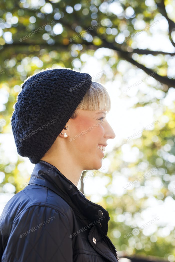 Side view of happy woman wearing knit hat