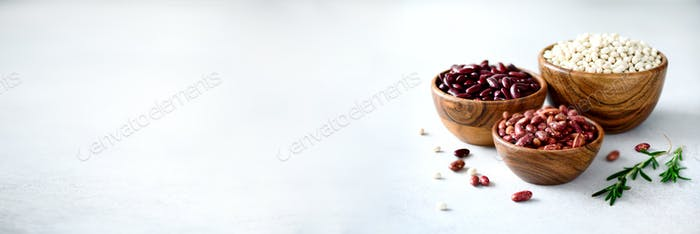 Various of kidney beans. Red, white and black kidney beans in wooden bowls with rosemary on grey