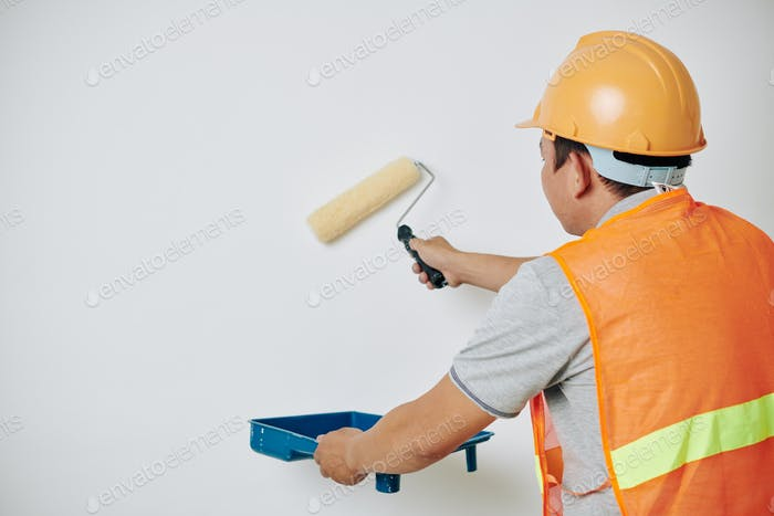 Painter applying white paint