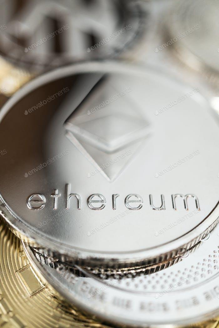 Nahaufnahme von Ether Physical Coin auf Stapel vieler anderer Kryptowährungen