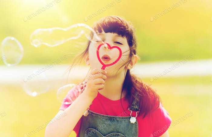 little girl blowing soap bubbles outdoors