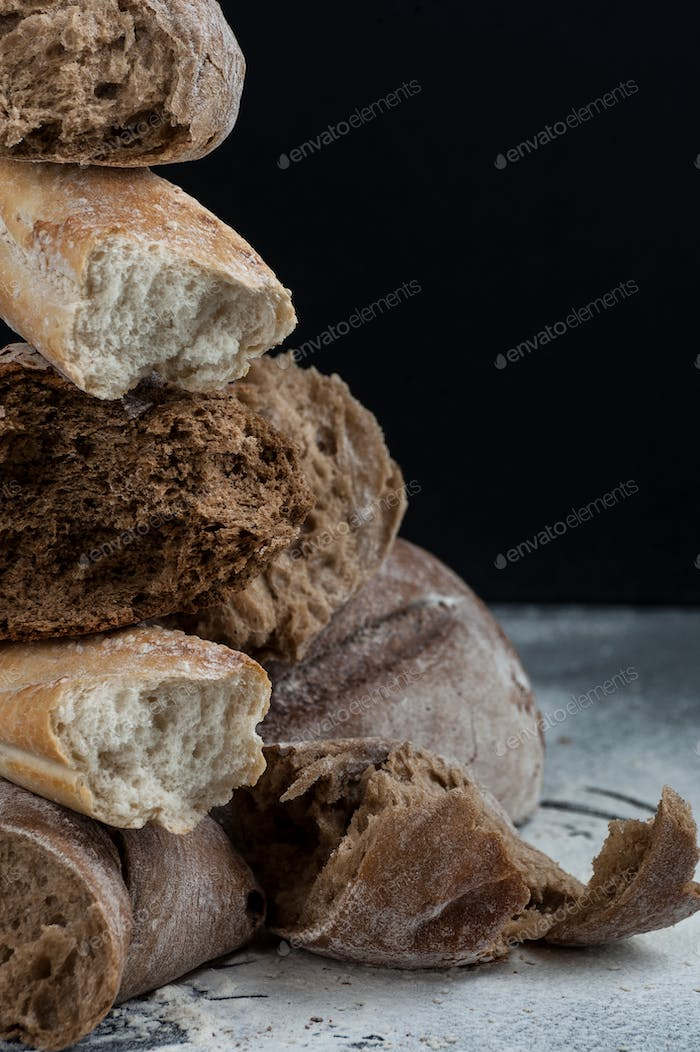 Pieces of different broken fresh bread close-up on a black backg