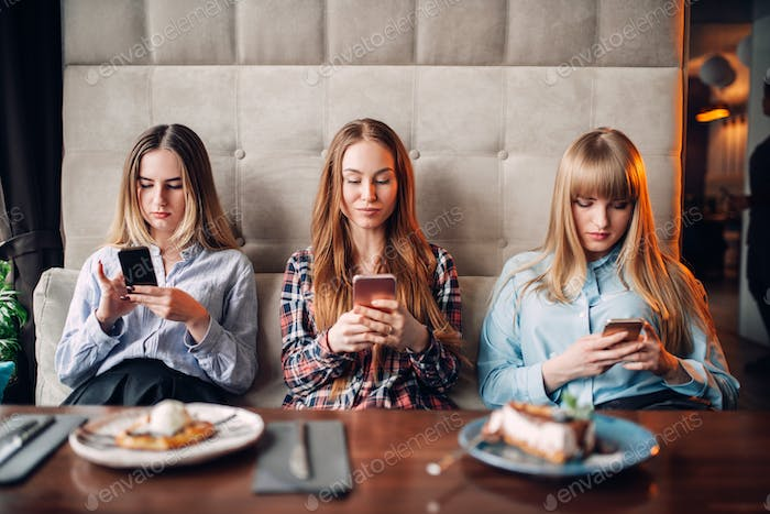 Three girls using mobile phones in cafe