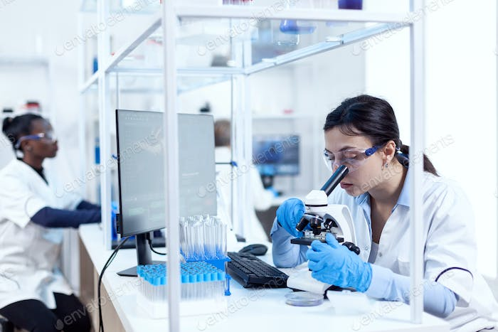 Expert in in genetics doing research using microscope