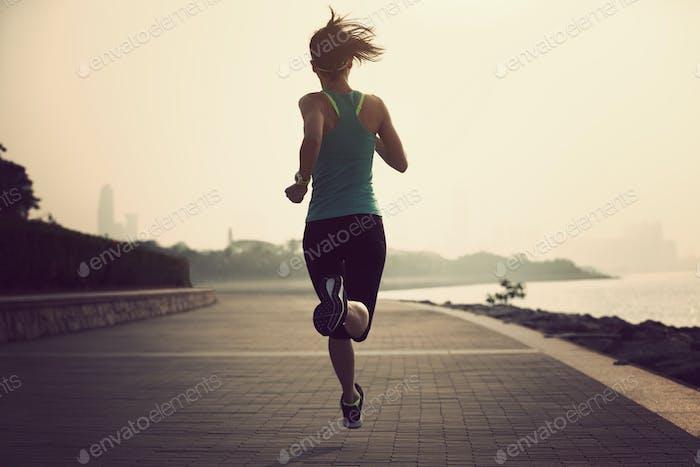 Fitness woman running on seaside