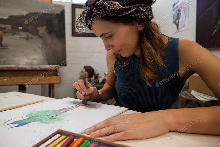 Женщина рисует на книге в классе рисования