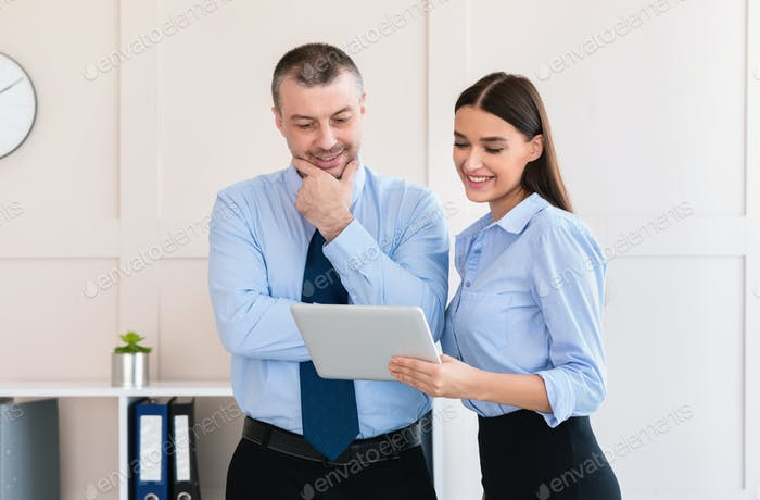 Бизнесмен показывает планшетный компьютер коллеге бизнесмен, стоящий в офисе