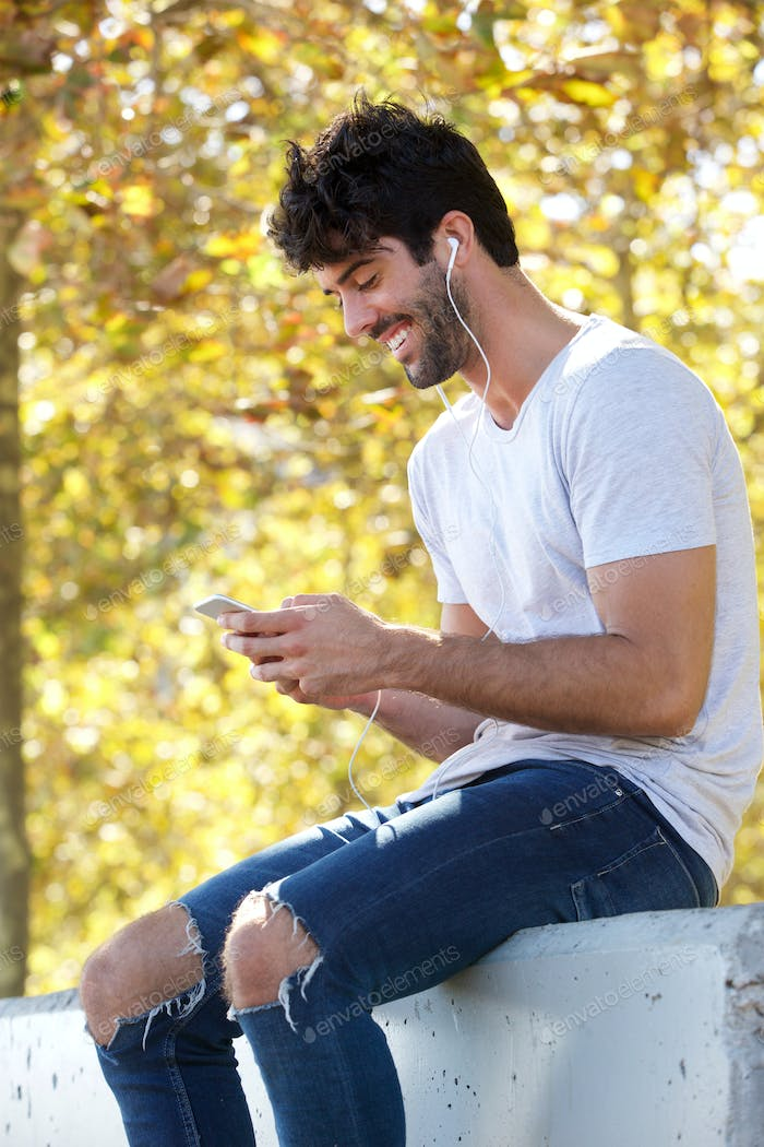 Smiling handsome man sitting outside with headphones and mobile phone