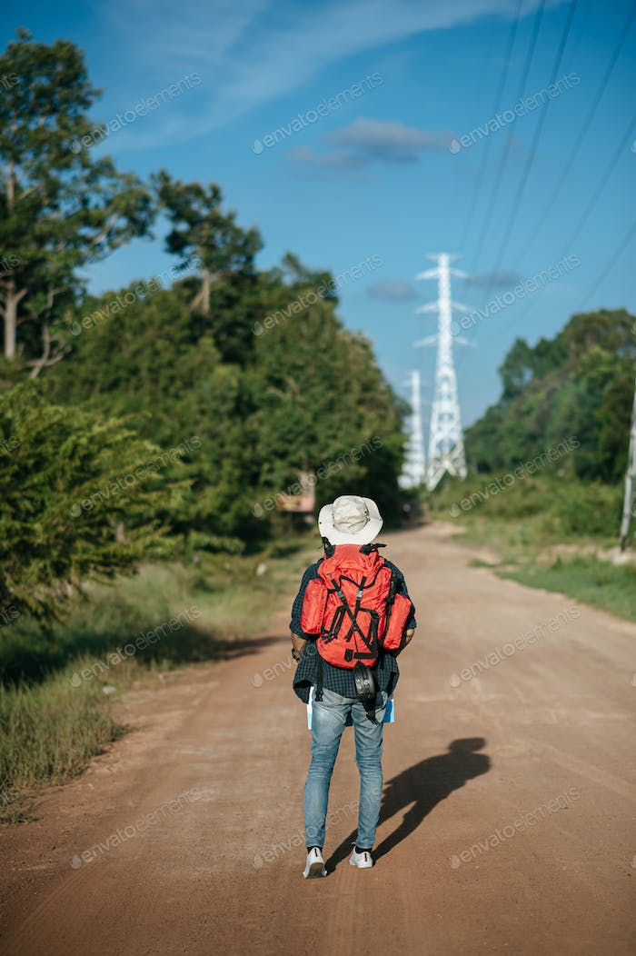Young backpacker man walking on street with map
