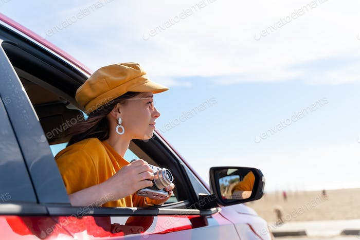 Young woman with a retro camera in the car