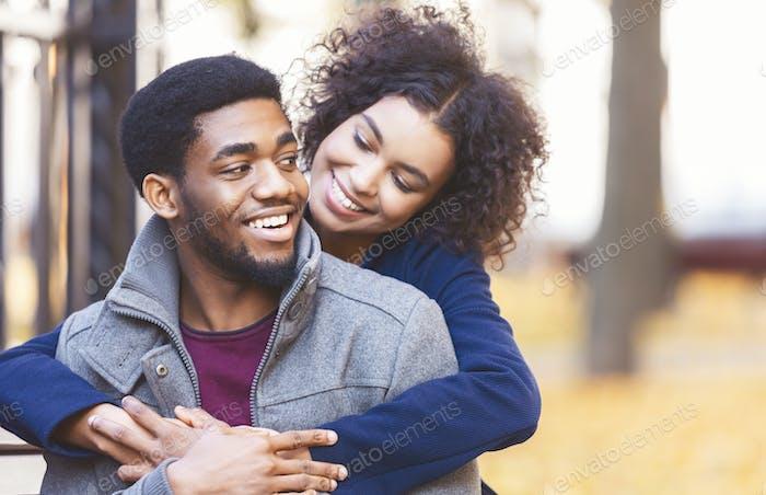 Cute black girl flirting with boyfriend, hugging from behind