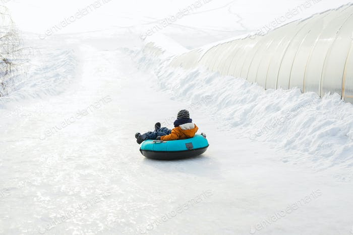 Little kid boy rolls down on ice slide on tubing. Wintertime. Fun and games, outdoor activities