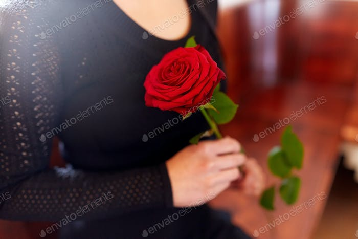 close up of woman with roses at funeral in church