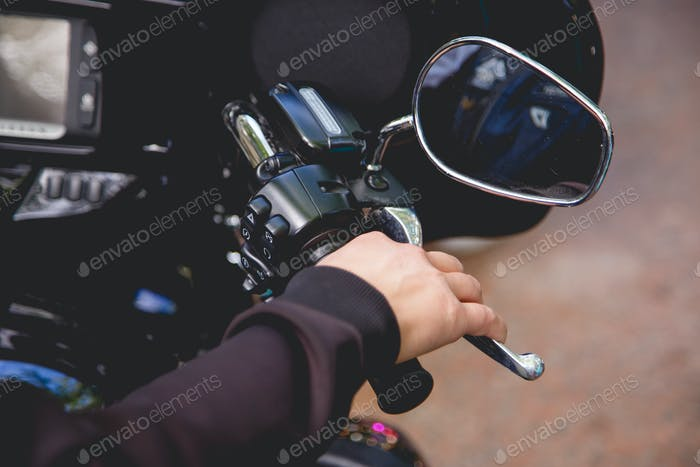 Close up Hand a man hold manual brake and stop running of motor cycle safety concept on the road