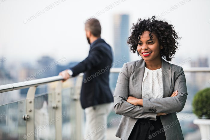 A portrait of a businesswoman standing on a terrace, arms crossed.