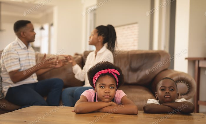 Portrait of sad African American children leaning on table while parents arguing on the sofa at home