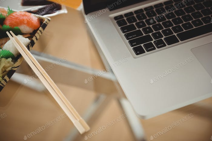 Close up of laptop by food on table