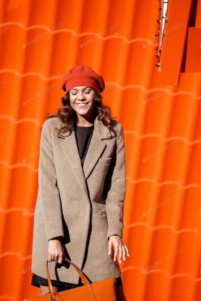 Stylish brunette girl dressed in a light brown coat and orange beret posing against the background