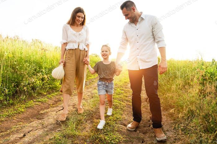 Glückliche Eltern und Kind zusammen im Sommer draußen zu Fuß