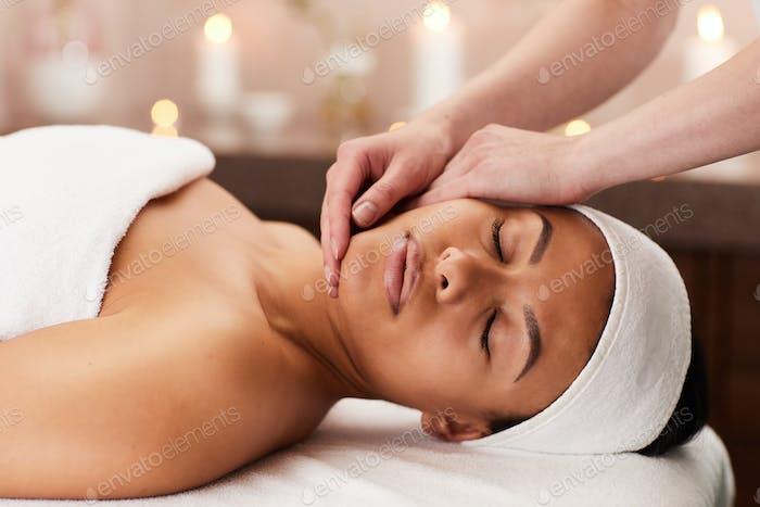 Woman Enjoying Face Massage in Spa