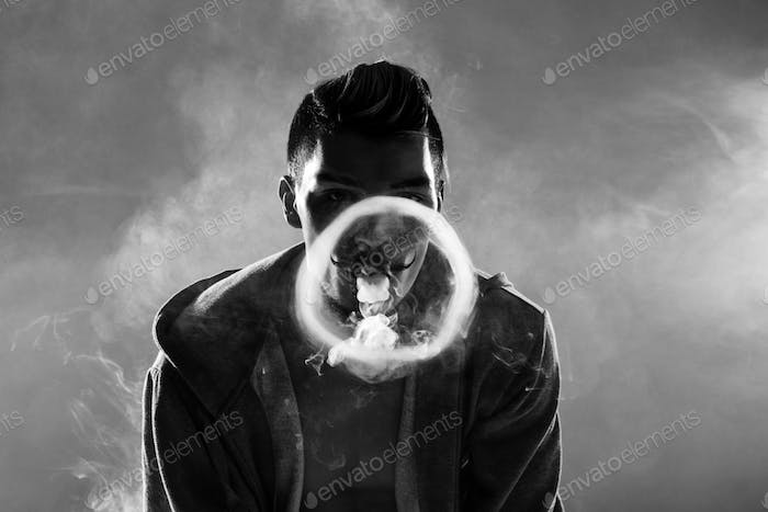 Black and white photo of young bearded man vaping and making circle from smoke