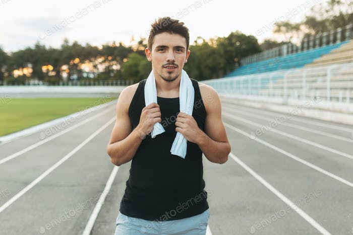 Portrait of a relaxing fitness man with towel on shoulders