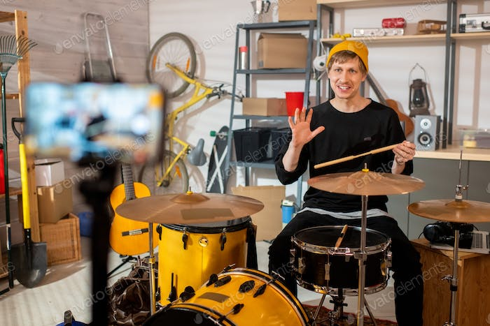 Happy young man with drumsticks sitting by drumset in front of smartphone camera