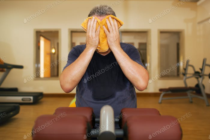 Man wiping face with a towel after training