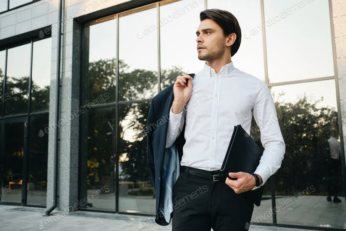Young handsome businessman in white shirt holding jacket on shoulder thoughtfully looking aside