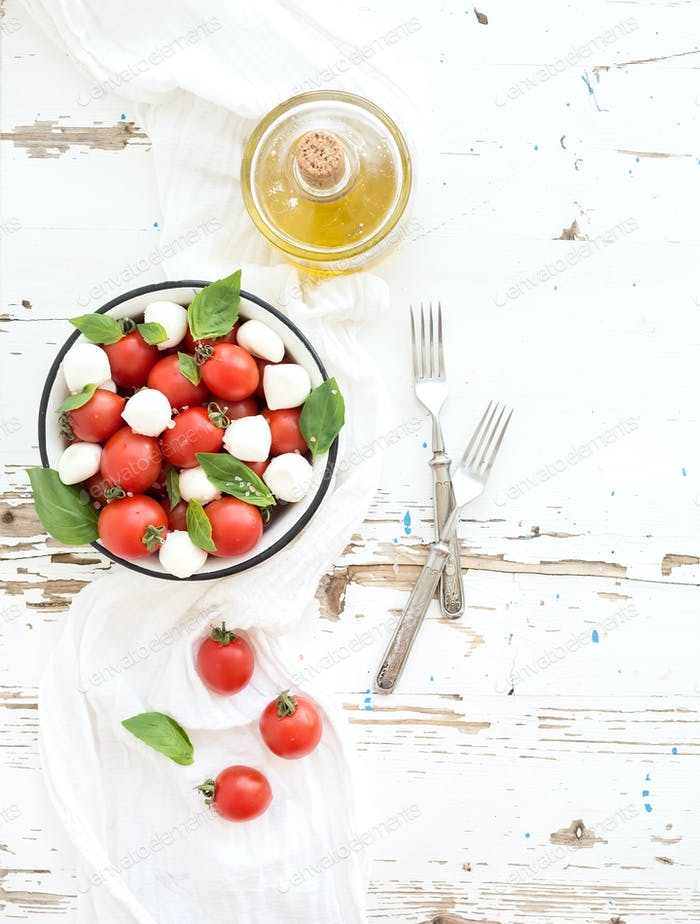 Caprese salad: cherry-tomatoes and mozzarella in metal bowl with olive oil