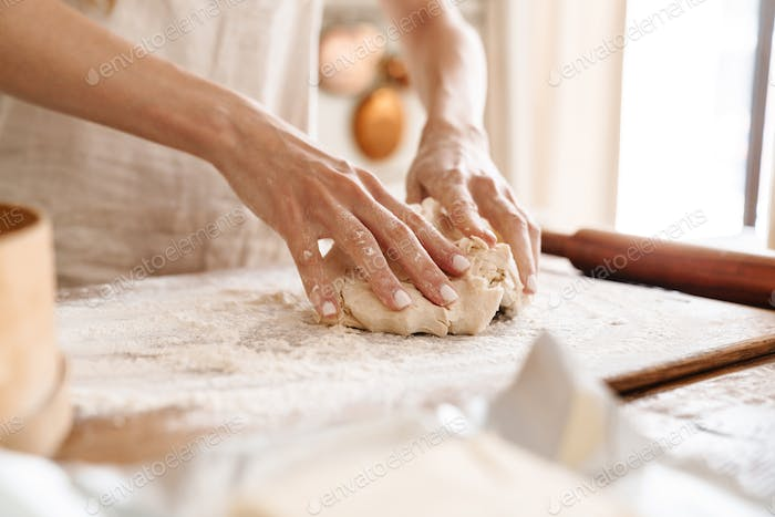 Close up of a young girl baking at the kitchen