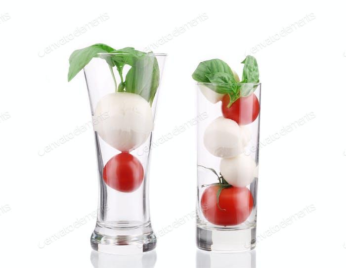 Tomatoes and mozzarella balls in glass.