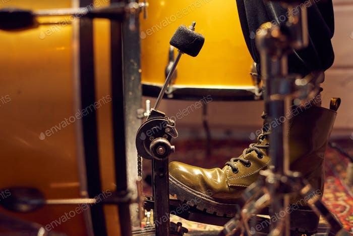 Part of leg of drummer on pedal of drum kit