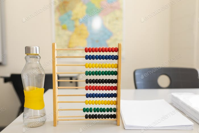 Close-up of water bottle, abacus and bunch of paper on the desk in school