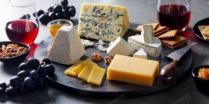 Käse-Sortiment auf dunklem Marmor Schneidebrett mit Rotwein. Grauer Hintergrund. Draufsicht.