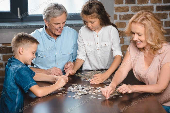 grandparents and grandchildren playing with puzzle together at home