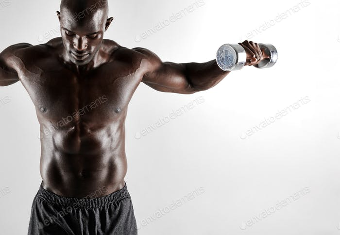 Male model exercising with dumbbells on grey background