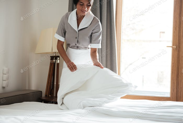 Maid setting up white bed sheet in hotel room