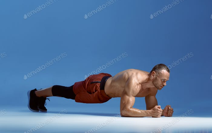 Male athlete trains his abs standing on his elbows