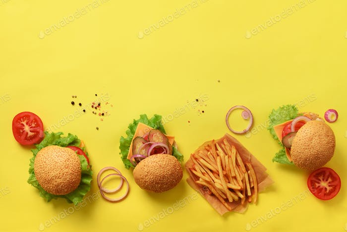 Tasty burgers with beef, tomato, cheese, onion, cucumber and lettuce on yellow background. Top view