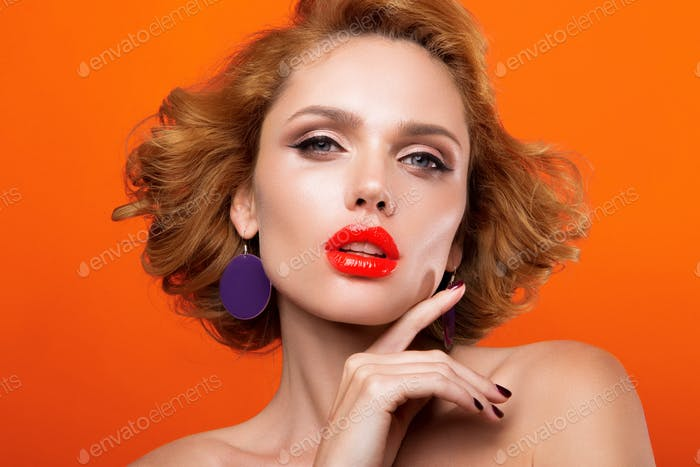 Beautiful young model with red lips, on a orange background