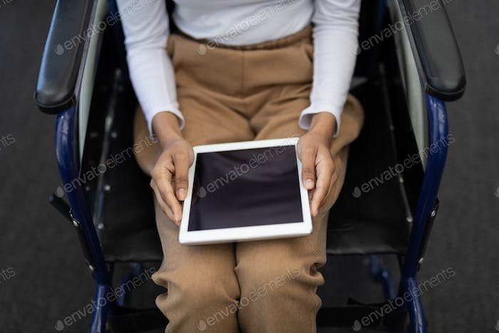 Mid section of disabled young mixed-race female executive using digital tablet in modern office