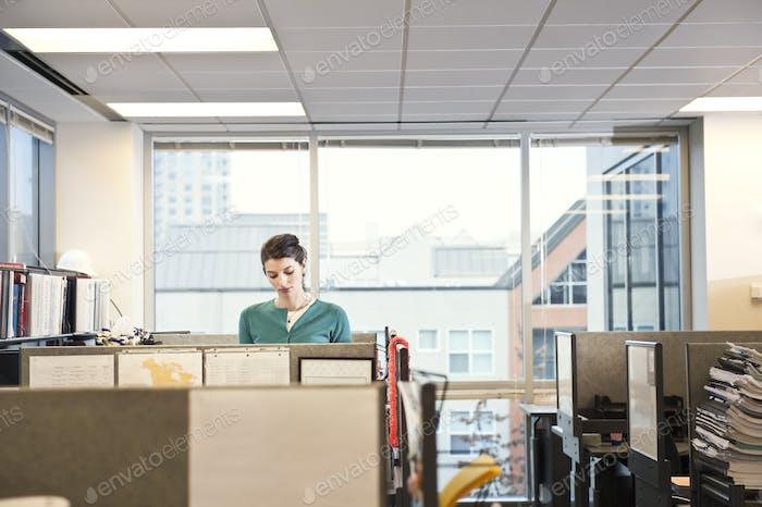 Eine junge kaukasische Geschäftsfrau, die in ihrer Kabine in einem Unternehmens- büro arbeitet.