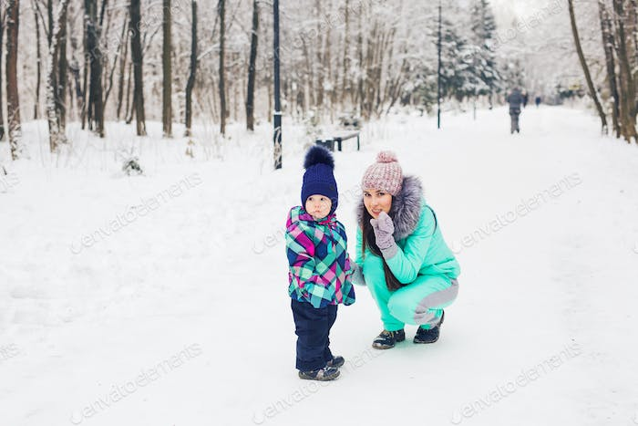 Family, parents and leisure concept - Mother and child girl having fun and playing in winter park