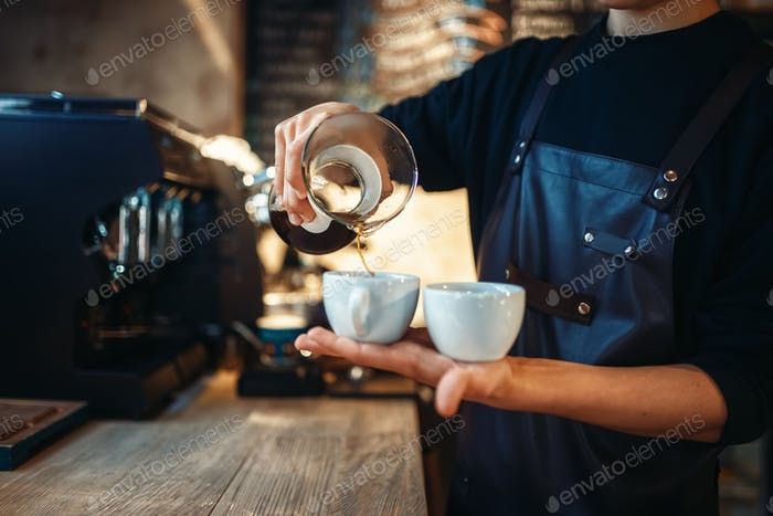 Young male barista holds two cups of fresh coffee