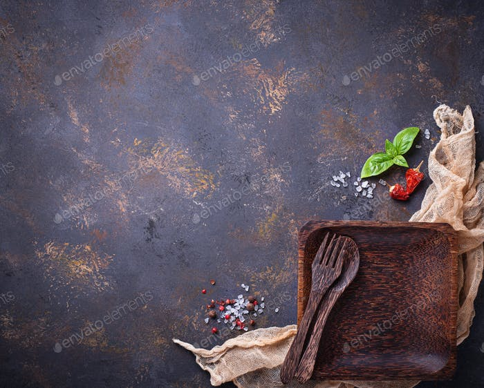 Empty wooden plate, cutlery, salt, pepper and basil