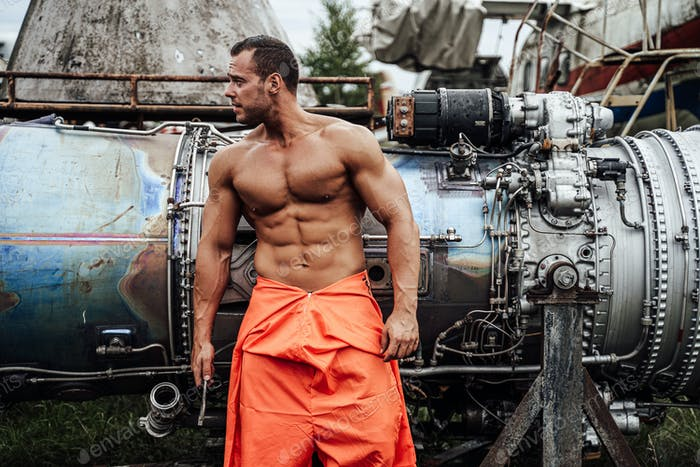 Mechanic macho with muscular build in orange clothing