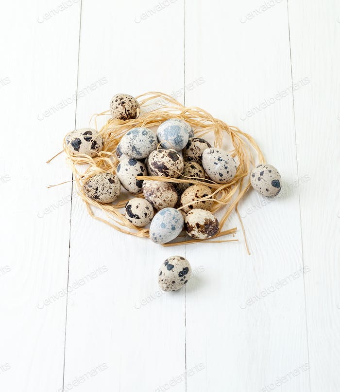 Fresh quail eggs and hay in a white wooden table.