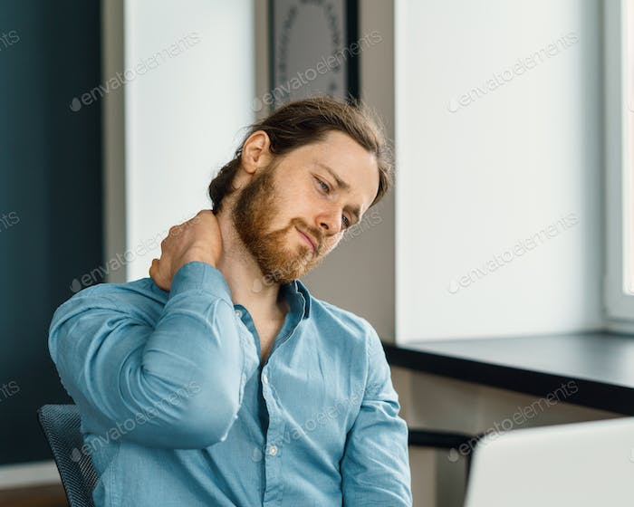 Tired office worker suffering from neck pain in office