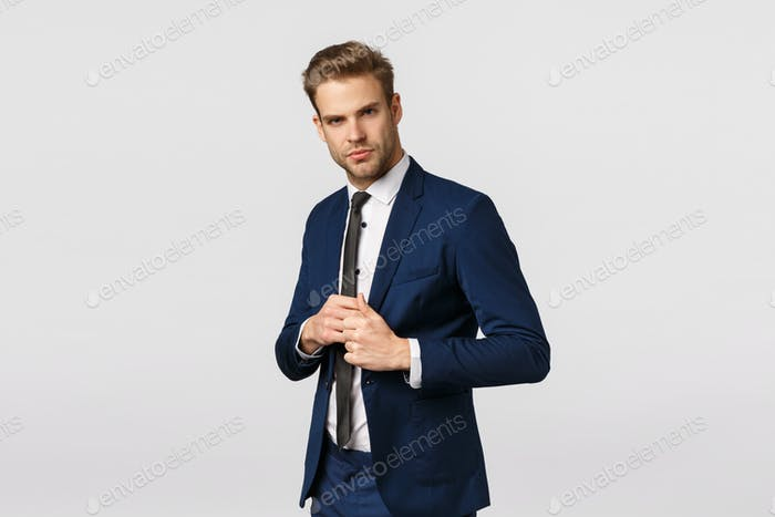 Determined, confident businessman in suit, fixing jacket, looking sassy and pleased camera, signed